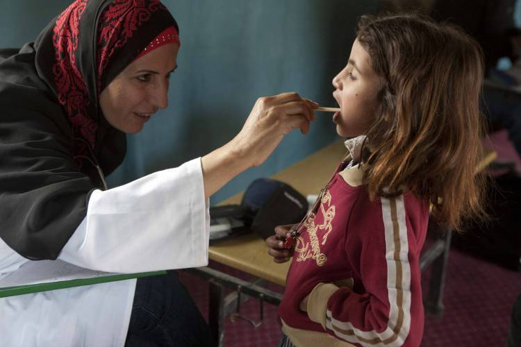 A nurse is examining a girl during one of the UNRWA mobile clinic visits in the West Bank. © 2011 UNRWA Photo by Maya Levin
