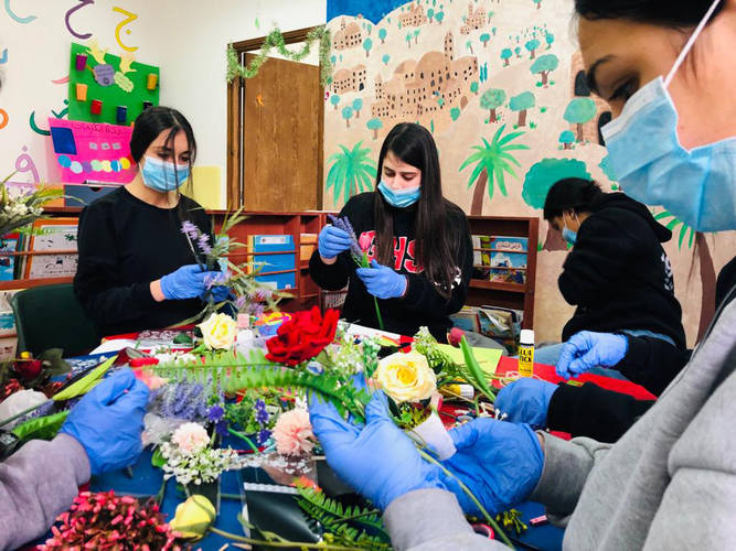 Young girls from the camp put together flowers to deliver to women around the camp for Arab Mother's Day on March 21, 2020.