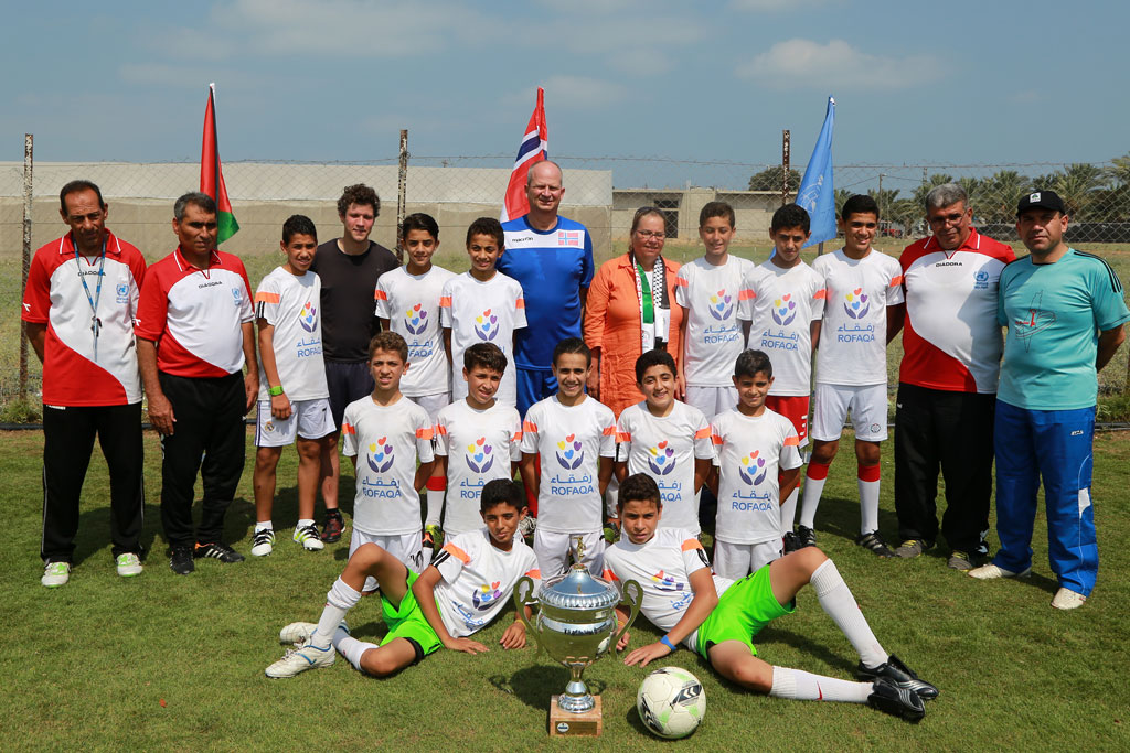 Head of the Representative Office of Norway to the Palestinian Authority, His Excellency. Hans Jacob Frydenlund (centre) poses for a photo with the winning youth football team after a friendly game at Al-Musader playground in Gaza. © 2016 UNRWA Photo by Rushdi Al Saraj