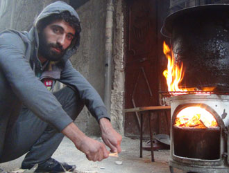 A Yarmouk resident warms himself by a makeshift stove. © UNRWA