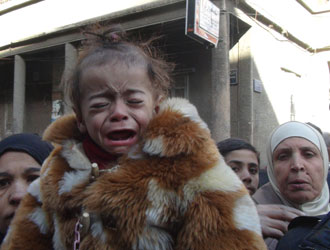 A malnourished child weeps on UNRWA's main street in February 2014. © UNRWA/Rami Al Sayed