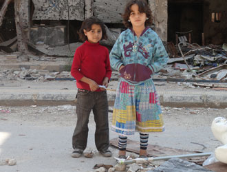 Two young girls stand on Rama Street, Yarmouk. © UNRWA/Rami Al Sayed