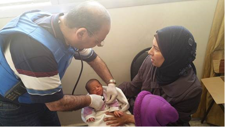 An UNRWA doctor assess a displaced family in Yalda, 9 May, 2015 ©UNRWA