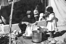 Archive photo of woman washing clothes outside tent