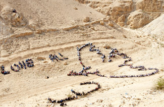Palestinian children form shape of dove of peace at Mount of Temptation, Jericho