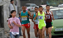 A Palestinian schoolgirl runs in front of participants in the Gaza marathon / AP
