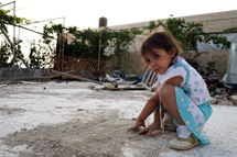 Girl playing outside her demolished home